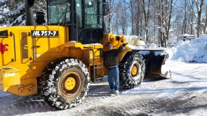 Community President Dennis Jakubowski directing the excavator to plow the community's roadways.